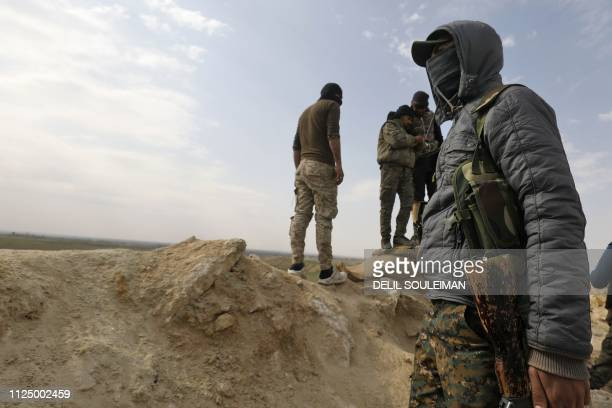 Fighters with the USbacked Syrian Democratic Forces keep a position during an operation to expel Islamic State group jihadists from the Baghouz area...