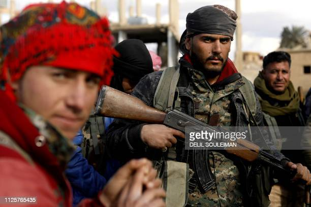 Fighters with the USbacked Syrian Democratic Forces take a rest in the frontline Syrian village of Baghouz on February 18 2018 SDF forces have been...