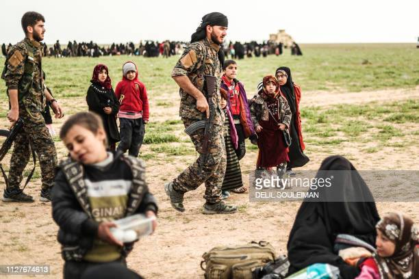 TOPSHOT Fighters with the USbacked Syrian Democratic Forces walk past civilians at a screening area for those who are evacuated from the Islamic...
