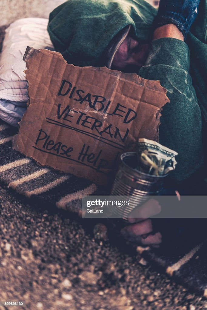 Fighting adversity. Homeless disabled veteran with sign and money tin : Stock Photo