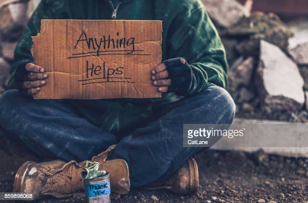 fighting adversity. homeless man with sign and money tin - homeless foto e immagini stock