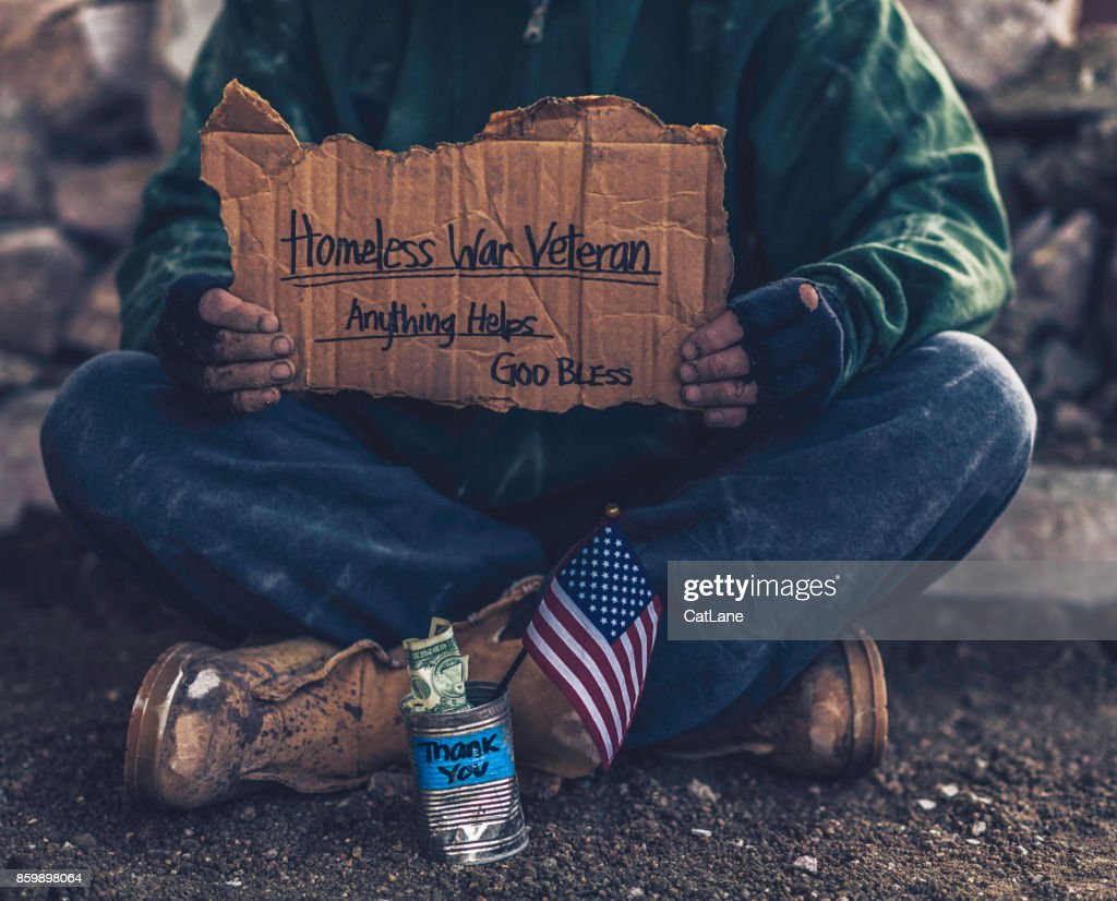 Fighting adversity. Homeless war veteran with sign and money tin : Stock Photo
