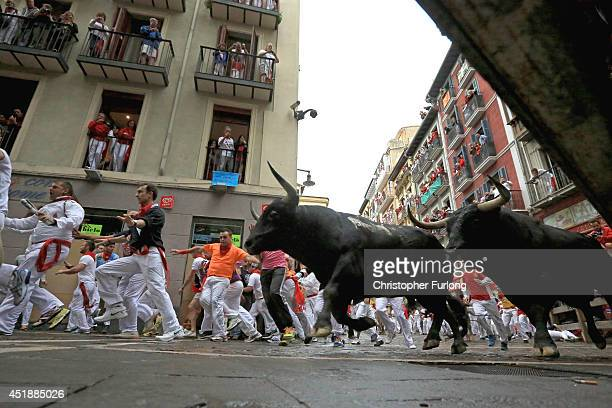 Fighting bulls from the ranch of Victoriano Del Rio Cortes run along the Curva de Estafetaa during the fourth day of the San Fermin Running Of The...