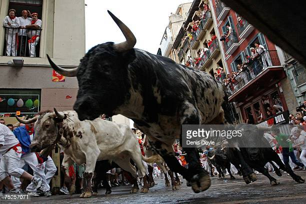 Fighting bulls take the corner at Estafeta Street behind running men during the first Running of the Bulls at the San Fermin fiesta on July 7 2007 in...