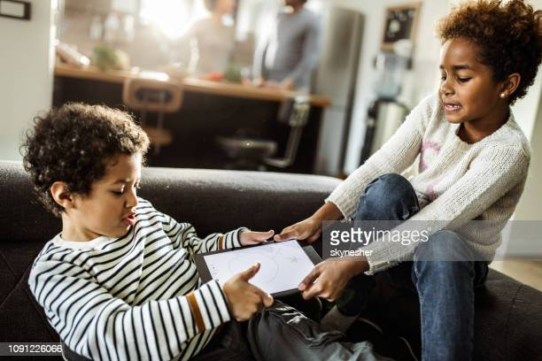 fighting over touchpad at home! - touchpad stock pictures, royalty-free photos & images