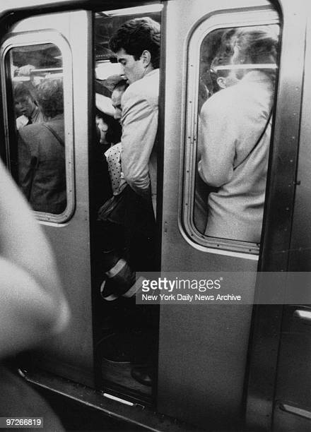 Fighting the crowd like everyone else, John F. Kennedy Jr. Squeezes into subway car after his first day on the job as assistant district attorney for...