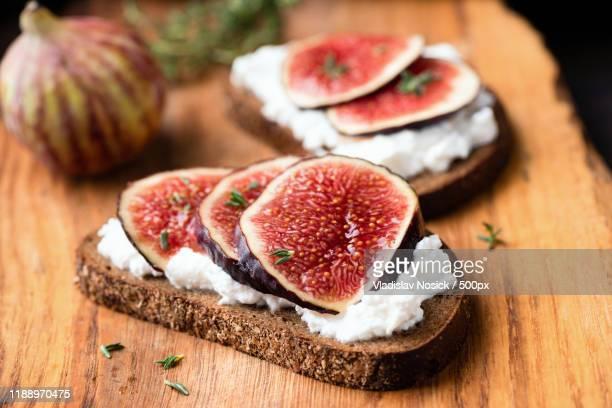 figs and soft white cheese on toasted rye bread - crosta di formaggio foto e immagini stock