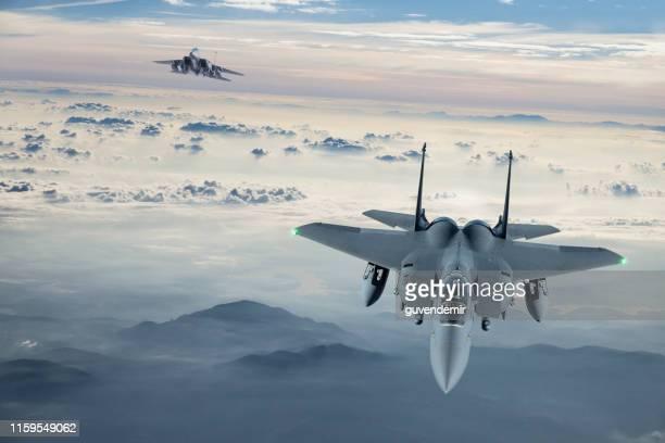 f-15 figter jet volando al atardecer - ejército de los estados unidos fotografías e imágenes de stock