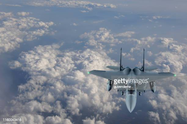 f-15 figter jet flying over clouds - air vehicle stock pictures, royalty-free photos & images