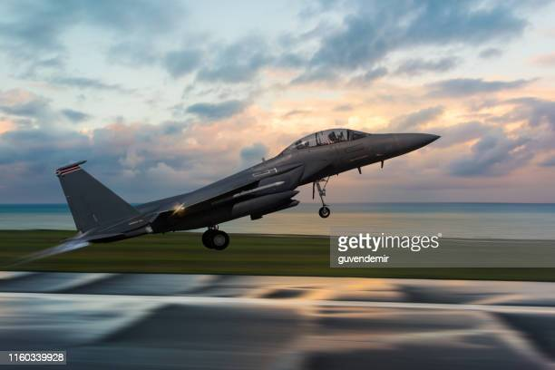 f-15 figter jet taking off at sunset - taking off activity stock pictures, royalty-free photos & images