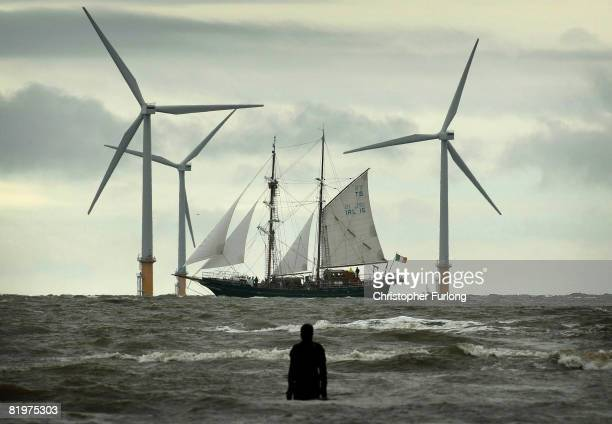A figure from Antony Gormley's 'Another Place' welcomes one of the Tall Ship to Merseyside as it sails past the Burbo Bank windfarm on the approach...