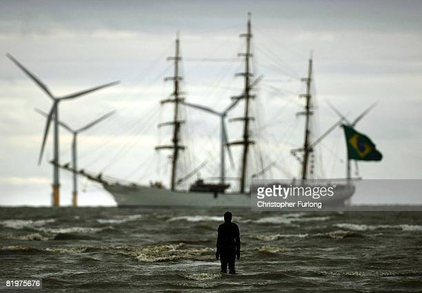 A figure from Antony Gormley's 'Another Place' welcomes one of the Tall Ships to Merseyside as it sails past the Burbo Bank windfarm on the approach...