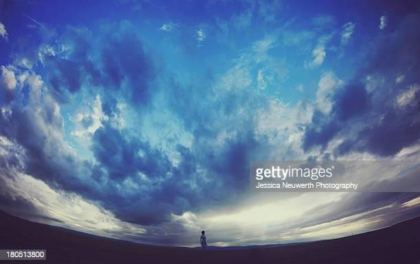 Figure in empty field beneath cloudy sky