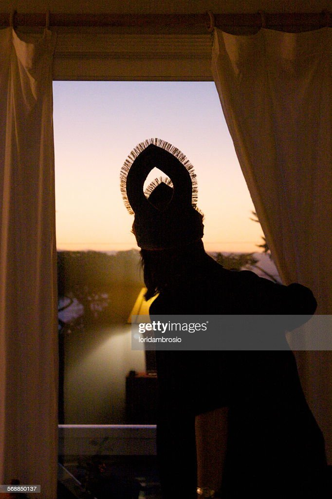 Figure looking out a window at sunset : Stock Photo