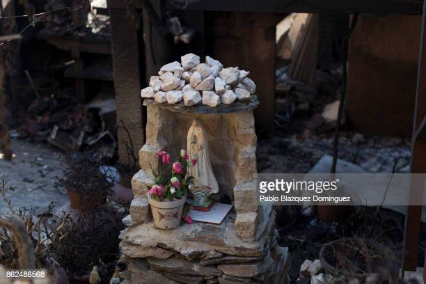 A figure of depicting the Virgin Mary stands at the entrance of a burnt house where a one woman died during a wildfire in the village of Travanca do...