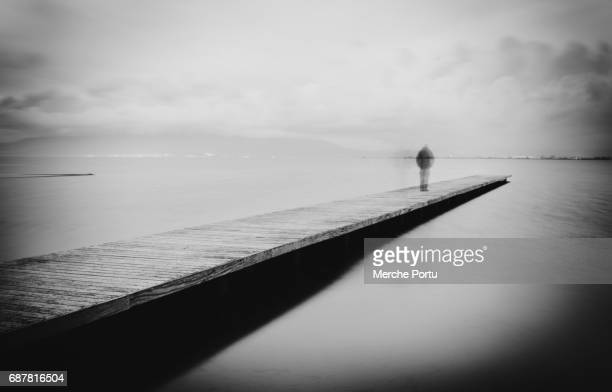 figure of man walking on a wooden walkway in the sea - suicidio fotografías e imágenes de stock