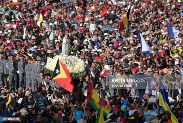 A figure representing Our Lady of Fatima is carried among the faithful at Fatima's Sanctuary central Portugal on May 13 2017 Two of the three child...