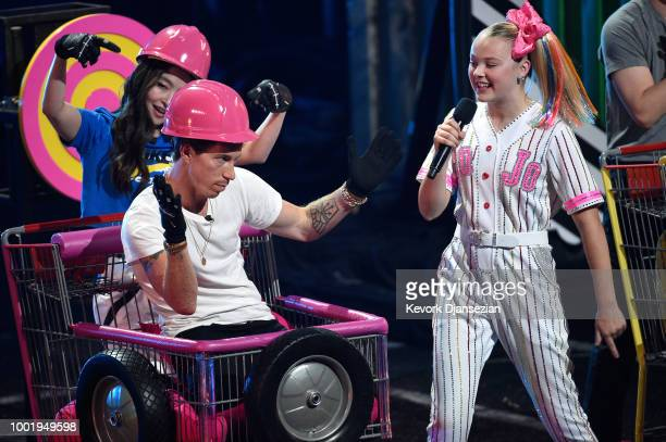 Figure skater Maia Shibutani snowboarder Shaun White and JoJo Siwa participate in a challange onstage during the Nickelodeon Kids' Choice Sports 2018...