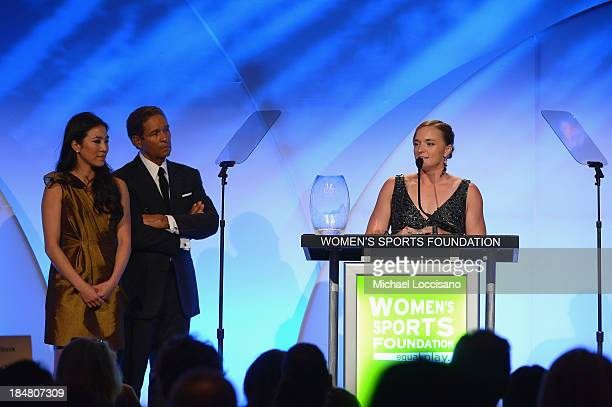 Figure skater Michelle Kwan and Bryant Gumbel present Paratriathlete Melissa Stockwell with the Wilma Rudolph Courage Award onstage during the 34th...