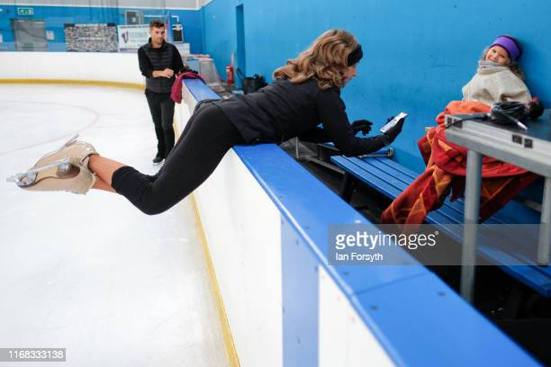 Figure skater Nina Ulanova leans over the barriers to speak with her daughter Kinzy during final rehearsals for the world premiere ice skating...