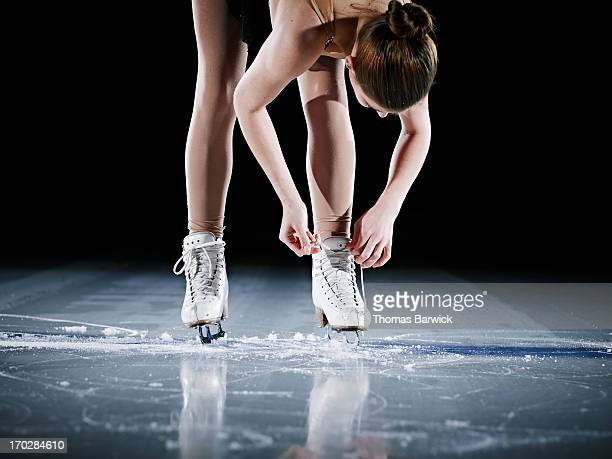 Figure skater standing on ice adjusting skate