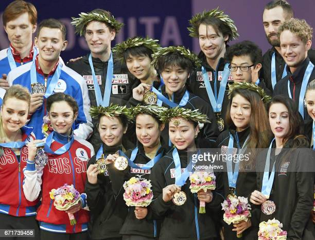Figure skaters from Japan Russia and the United States pose on the podium after winning the gold silver and bronze medals respectively at the World...