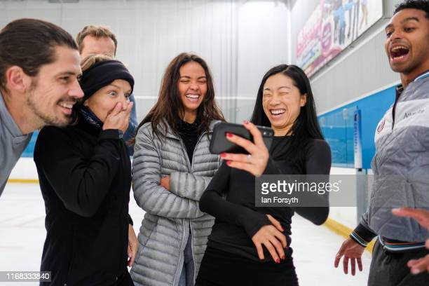 Figure skaters John Kerr Nina Ulanova Vanessa Bauer Yebin Mok and Oscar Peter react as they watch a video during a break at final rehearsals for the...