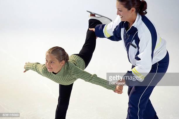 figure skating coach and girl - eiskunstlauf stock-fotos und bilder