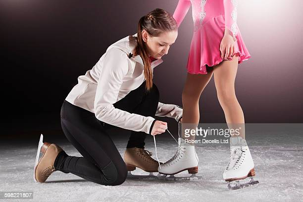 Figure skating coach doing up pupil's laces