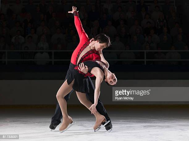 figure skating pair standing in finishing pose - figure skating stock pictures, royalty-free photos & images