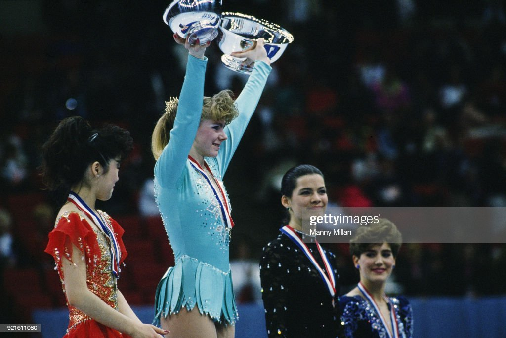 Closeup of (L-R) Kristi Yamaguchi, Tonya Harding, and Nancy Kerrigan victorious on medal stand with flowers after event at Target Center. Manny Millan X41033 )