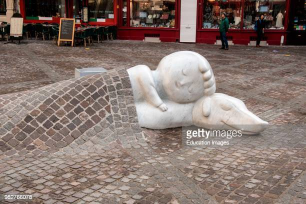 Figures if child and dog sleep soundly under pavement in a square Antwerp Belgium