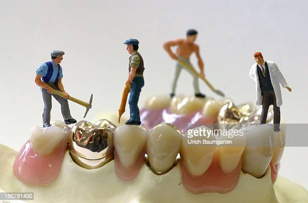 Figures of building workers and a doctor on dentures Symbolic photo to the topic building site health service reform