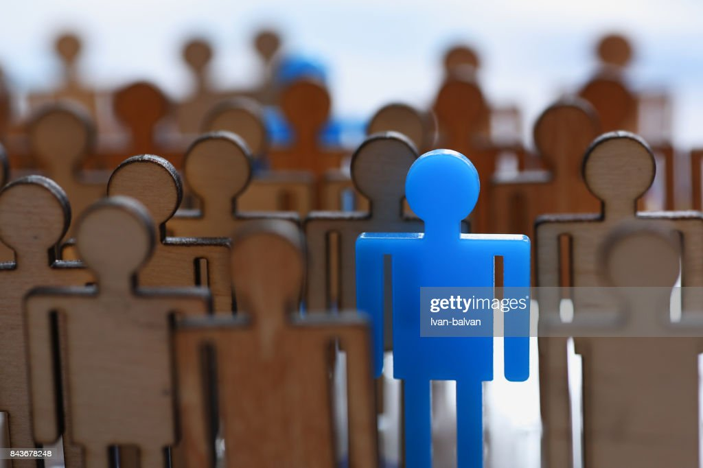 Figurine blue man in the crowd of wooden figures : Stock Photo