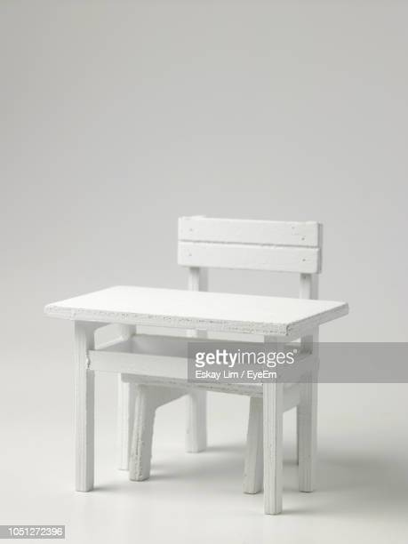Figurine Chair And Table Against White Background
