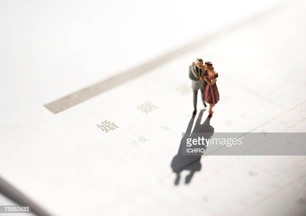 Figurine couple on marriage certificate