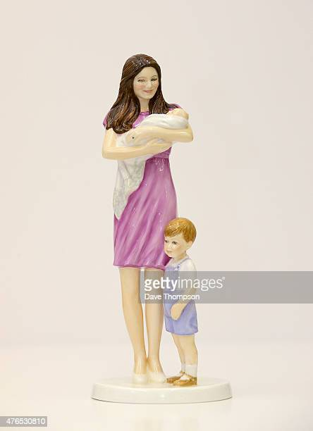 A figurine designed by artist Neil Faulkner of HRH Princess Charlotte of Cambridge held by her mother Catherine Duchess of Cambridge standing...