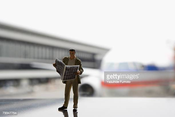 Figurine man reading newspaper in airport