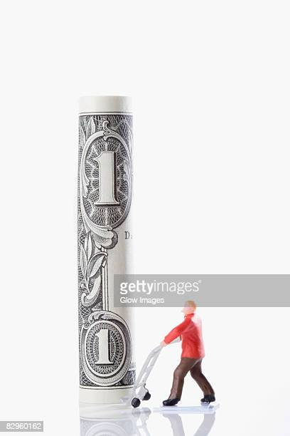 figurine of a manual worker carrying a rolled up us paper currency on a push cart - rolled up stock pictures, royalty-free photos & images