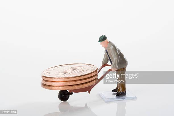 Figurine of a manual worker carrying coins on a wheelbarrow