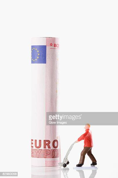 Figurine of a manual worker carrying European union euro note on a push cart