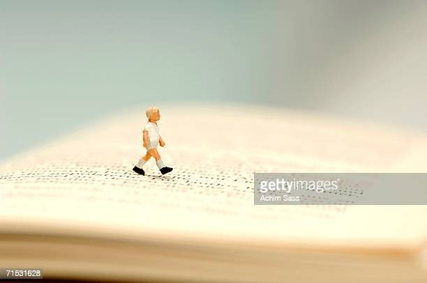 Figurine of boy walking on open book, close-up