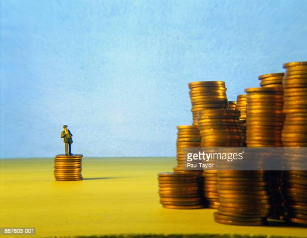 Figurine of businessman looking at stacks of coins