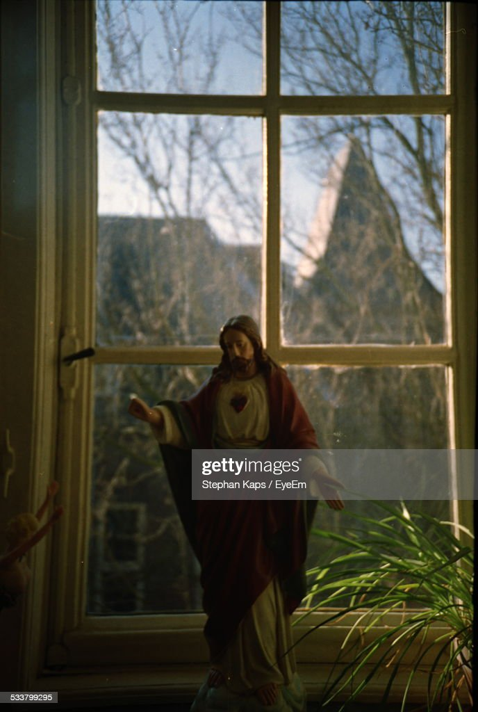 Figurine Of Christ Against Window : Foto stock