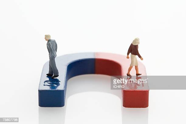 figurine of man and woman on magnet - horseshoe magnet stock pictures, royalty-free photos & images
