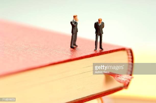 Two figurine of men standing on book, close-up