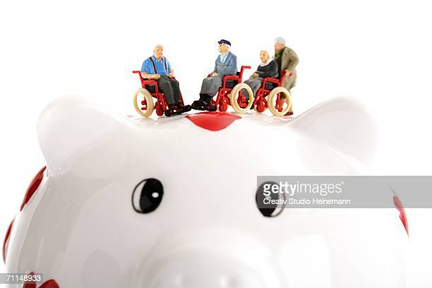 Figurine on wheelchairs on piggy bank