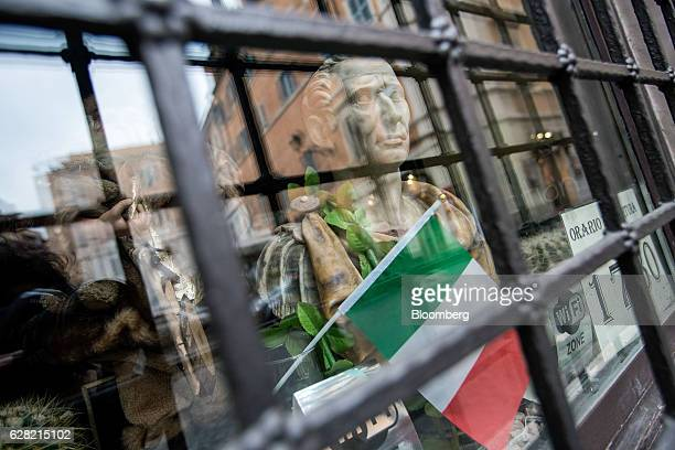A figurine representing Julius Cesar and Italy's national flag stand displayed in a shop window in Rome Italy on Tuesday Dec 6 2016 Market reaction...