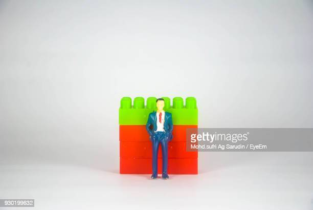 Figurine Standing In Front Of Blocks Against White Background