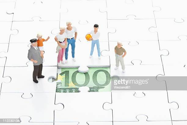 Figurine standing on jigsaw piece and watching 100 euro note